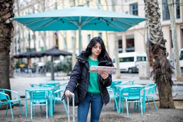 Portret van gelukkige mooie toevallige vrouwenreiziger die richting op locatiekaart zoeken