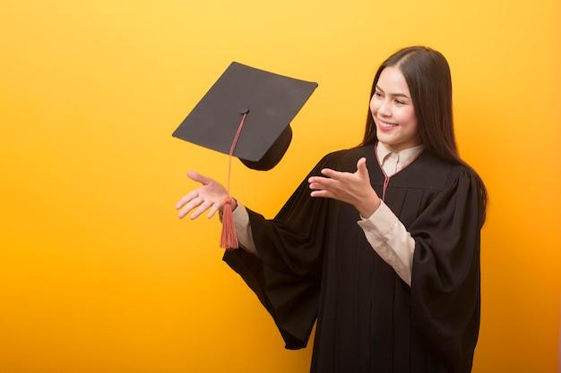 Portret van gelukkige mooie vrouw in graduatietoga op gele ruimte