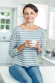 Portret van gelukkige mooie vrouw met koffie