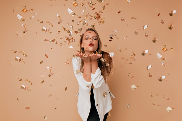 Portret van gelukkige mooie vrouw stuurt een kus op geïsoleerde muur met confetti. gelukkige viering van nieuw jaar, verjaardag