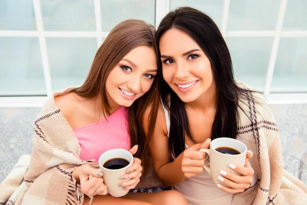 Portret van gelukkige mooie vrouwen met plaid en hete koffie