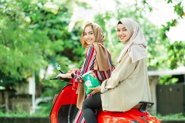 Portret van gelukkige moslimmeisjes rijden scooter genieten van zomervakantie met vrienden