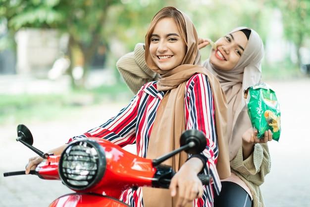 Portret van gelukkige moslimvriend motorfiets scooter samen buiten rijden
