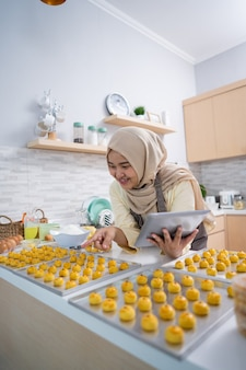 Portret van gelukkige moslimvrouw met nastarsnack in de keuken