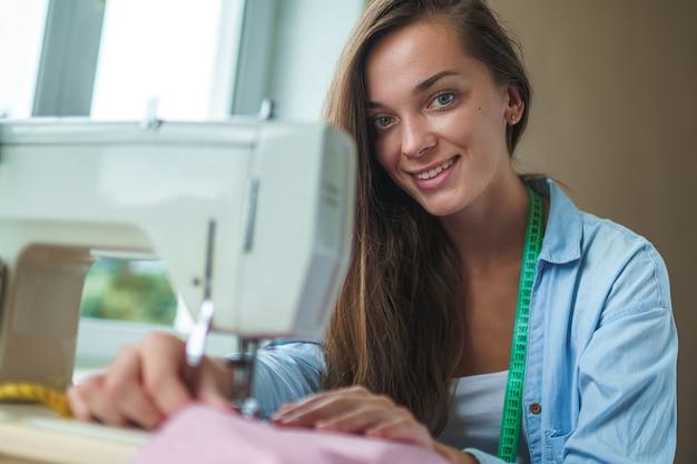 Portret van gelukkige naaister met elektrische naaimachine en verschillende naaiende accessoires voor het naaien van kleding
