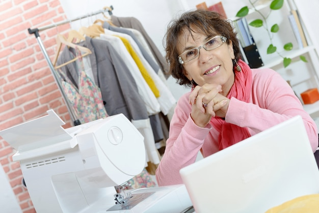 Portret van gelukkige naaistervrouw in studio