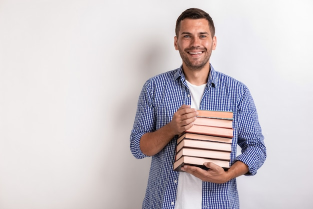 Portret van gelukkige nerd jonge man met boeken in zijn handen. terug naar school