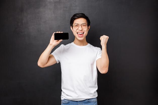 Portret van gelukkige opgewonden aziatische man die geld wint op sportweddenschap, vuistpomp en viert, zijn beste score in mobiel spel laat zien, smartphone vasthoudt en zegeviert,