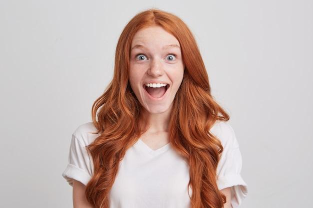 Portret van gelukkige opgewonden roodharige jonge vrouw met lang haar