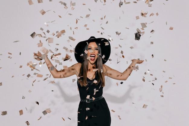 Portret van gelukkige opgewonden vrouw, gekleed in zwarte avondjurk en een hoed confetti gooien over geïsoleerde muur met echte gelukkige emoties.