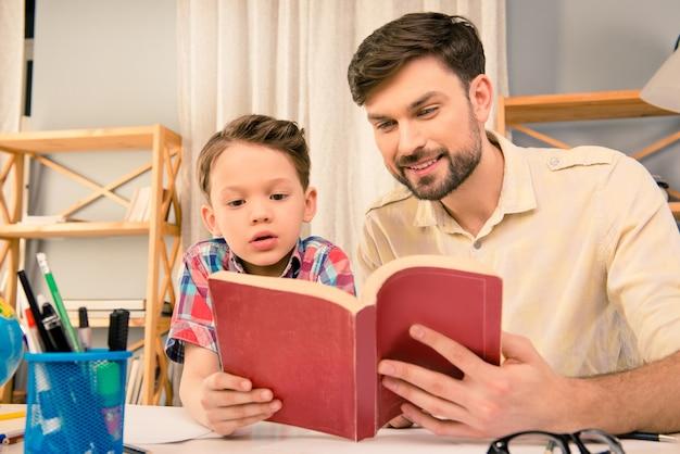 Portret van gelukkige ouder en zijn zoon die sprookjes lezen