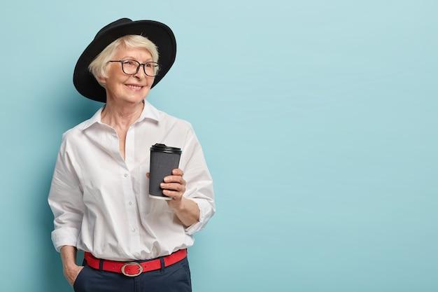 Portret van gelukkige oudere vrouw met pensioen, heeft een ontmoeting met voormalige collega's, houdt afhaalkoffie, draagt stijlvol wit overhemd, broek met rode riem, houdt hand in zak. vrije tijd, pensioen