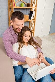 Portret van gelukkige paar die met computer thuis werken