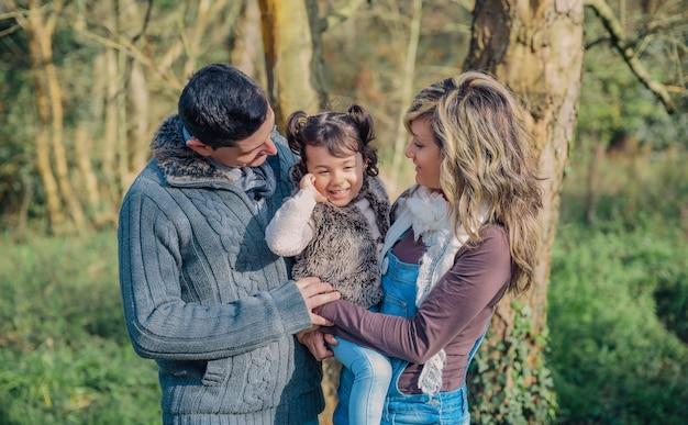 Portret van gelukkige paar met haar dochtertje samen genieten van vrije tijd over een bos. familie tijd concept.