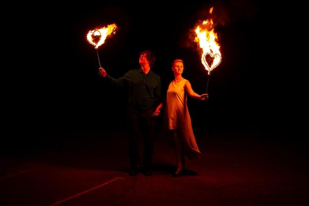 Portret van gelukkige paar met vuur in hun handen. ze hebben een geweldige tijd samen Premium Foto