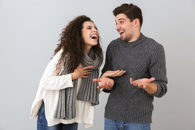 Portret van gelukkige paarman en vrouw die en met elkaar glimlachen praten, geïsoleerd over grijze muur