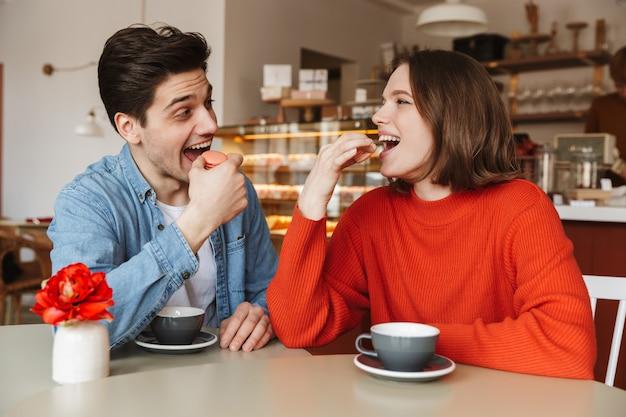 Portret van gelukkige paarman en vrouw die in gezellige bakkerij daten, en macaronkoekjes eten