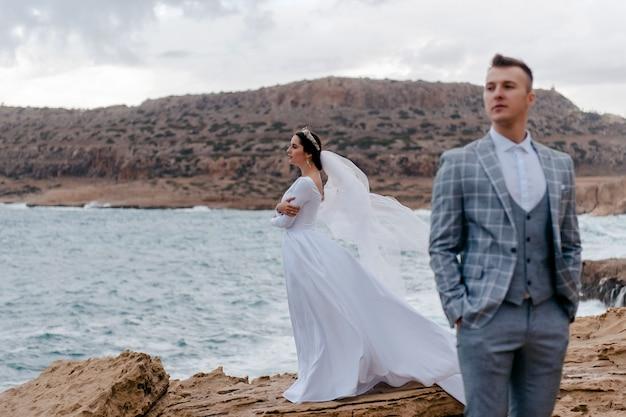 Portret van gelukkige pasgetrouwden, bruid en bruidegom, staande op een rotsachtige kust in de buurt van de zee the