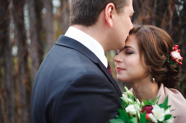 Portret van gelukkige pasgetrouwden in de herfst de natuur. gelukkige en bruid en bruidegom die omhelzen kussen