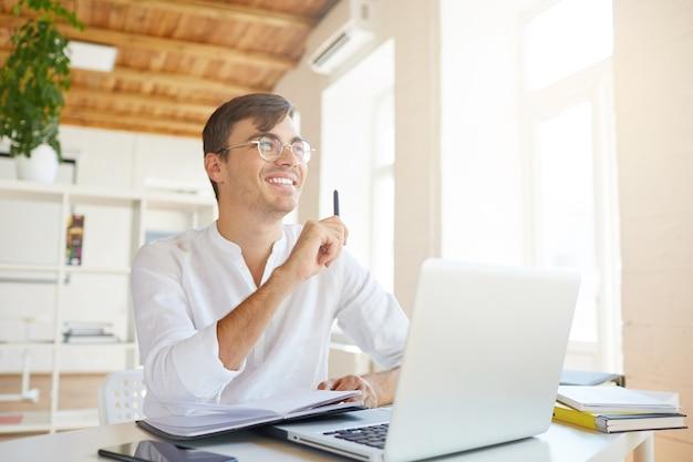 Portret van gelukkige peinzende jonge zakenman draagt een wit overhemd op kantoor