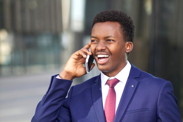 Portret van gelukkige positieve opgewonden zakenman die op zijn celtelefoon spreekt