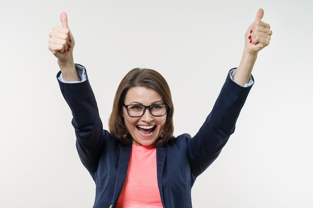 Portret van gelukkige rijpe onderneemster met omhoog duimen