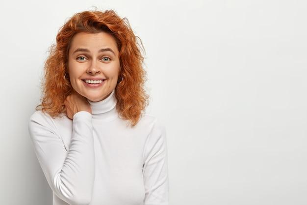 Portret van gelukkige roodharige gekrulde vrouw voelt zich enthousiast en geamuseerd, raakt de nek zachtjes aan, lacht zachtjes, heeft een leuk vriendelijk gesprek, poseert binnen tegen een witte muur