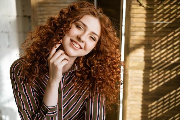 Portret van gelukkige roodharige krullende jonge vrouw dichtbij venster het glimlachen