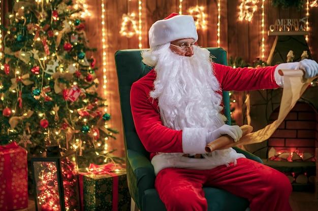 Portret van gelukkige santa claus-zitting thuis bij zijn ruimte dichtbij kerstboom en lezingskerstmisbrief of wenslijst