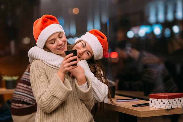 Portret van gelukkige schattige jonge vrienden die elkaar knuffelen bij caffe
