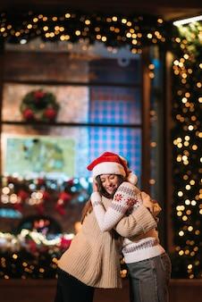 Portret van gelukkige schattige jonge vrienden die elkaar knuffelen en glimlachen tijdens het wandelen op kerstavond buitenshuis.