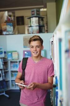 Portret van gelukkige schooljongen die digitale tablet in bibliotheek houdt