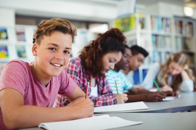 Portret van gelukkige schooljongen die in bibliotheek bestudeert