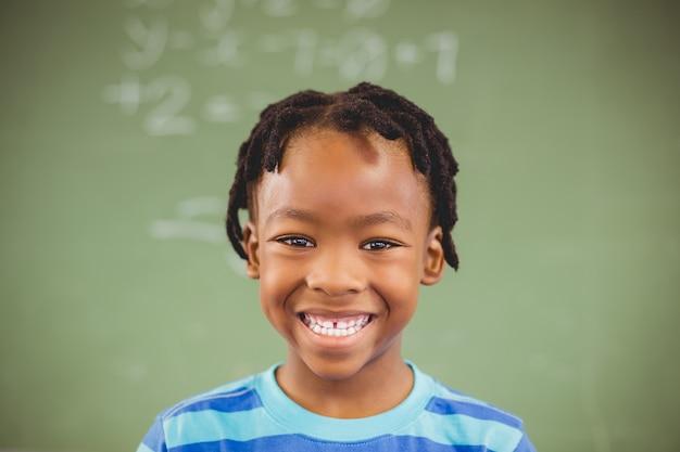 Portret van gelukkige schooljongen die in klaslokaal glimlachen