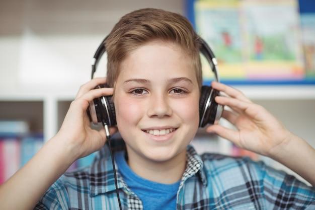 Portret van gelukkige schooljongen luisteren muziek op koptelefoon in bibliotheek