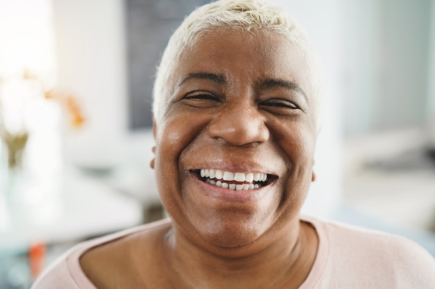 Portret van gelukkige senior afrikaanse vrouw kijken camera binnenshuis thuis - focus op gezicht
