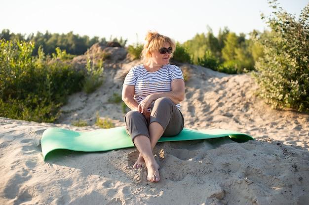 Portret van gelukkige senior mooie vrouw zittend op een zand in zomer strand