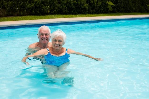 Portret van gelukkige senior paar in het zwembad op een zonnige dag