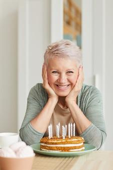 Portret van gelukkige senior vrouw zitten aan de tafel met cake met kaarsen en glimlachend in de camera