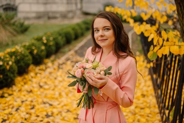 Portret van gelukkige sensuele jonge donkerbruine bruid in roze huwelijkskleding en status in de herfstpark dichtbij uitstekende kathedraal en het houden van huwelijksboeket.