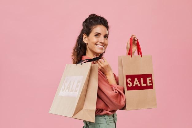 Portret van gelukkige shopaholic die boodschappen doet in de uitverkoop die ze glimlachend en boodschappentassen vasthoudt