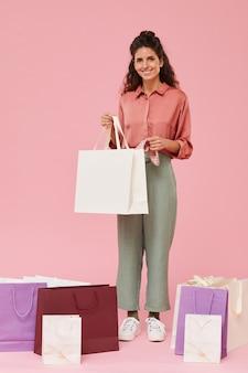 Portret van gelukkige shopaholic papieren zak met aankoop houden en glimlachen geïsoleerd op roze achtergrond