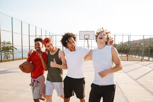 Portret van gelukkige sportieve mannen basketbalspelers wandelen langs speelplaats buiten, tijdens zonnige zomerdag