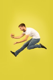 Portret van gelukkige springende man op gele muur