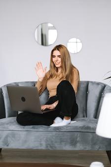 Portret van gelukkige stijlvolle jonge vrouw zittend op een bank, laptop scherm kijken op videogesprek en groet met zwaaien.