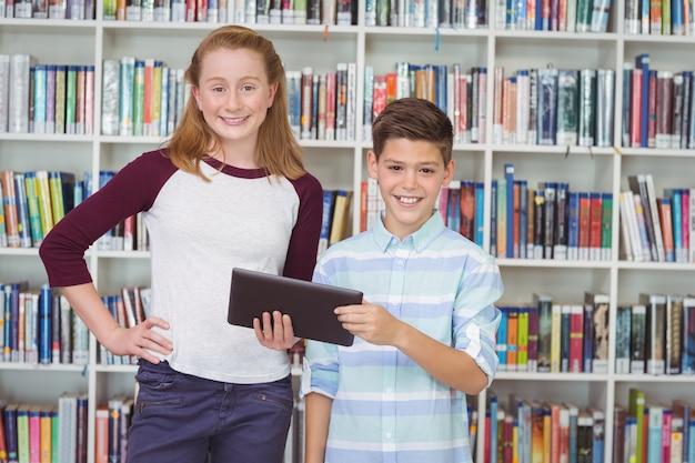 Portret van gelukkige studenten die digitale tablet in bibliotheek houden