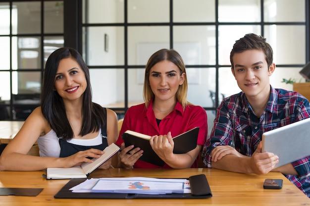 Portret van gelukkige studenten die met handboeken en pc-tablet zitten