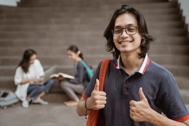 Portret van gelukkige studenten die zak houden en duimen met vrienden op de achtergrond tonen