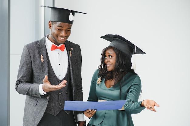 Portret van gelukkige studenten met diploma's op de afstudeerdag