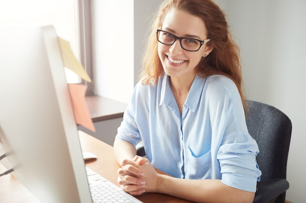 Portret van gelukkige succesvolle kaukasische onderneemster in blauw overhemd en glazen